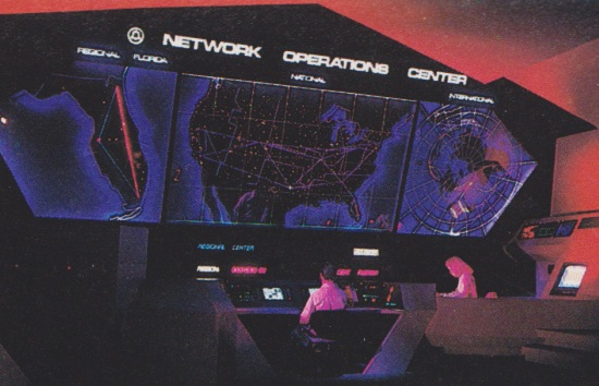 Vintage Spaceship Earth Scene with addition of Bell logo featuring two animatronics at a Network Operations Center with a large digital map on a wall and control panels at a desk